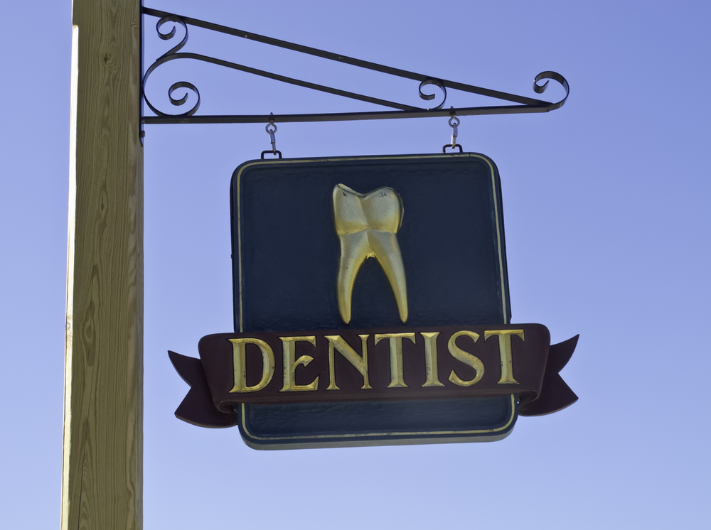 Dentists sign with gold tooth against a blue sky
