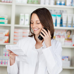 Mid adult female pharmacist holding prescription paper while using cordless phone in pharmacy