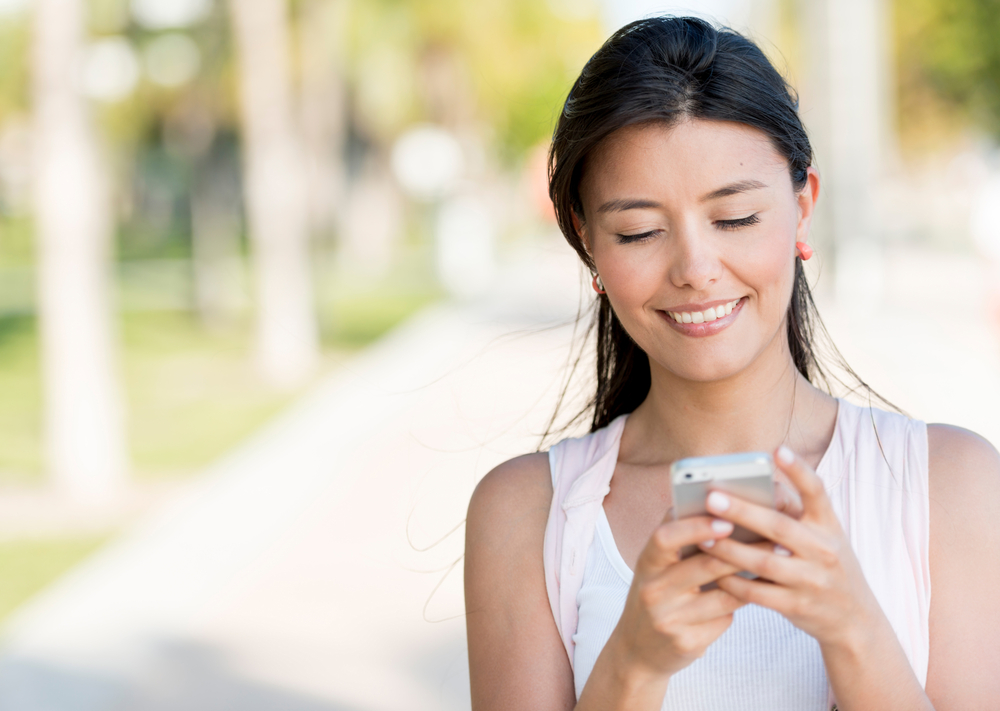 Portrait of a woman sending text message from her phone