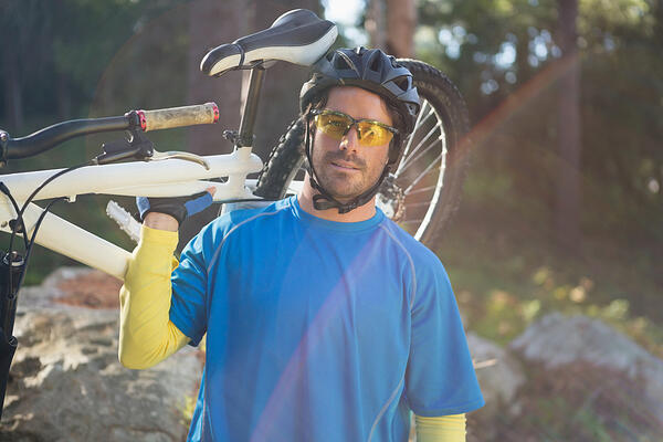 Portrait of male mountain biker carrying bicycle in the forest on a sunny day