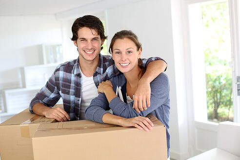 Smiling couple leaning on boxes in new home-1