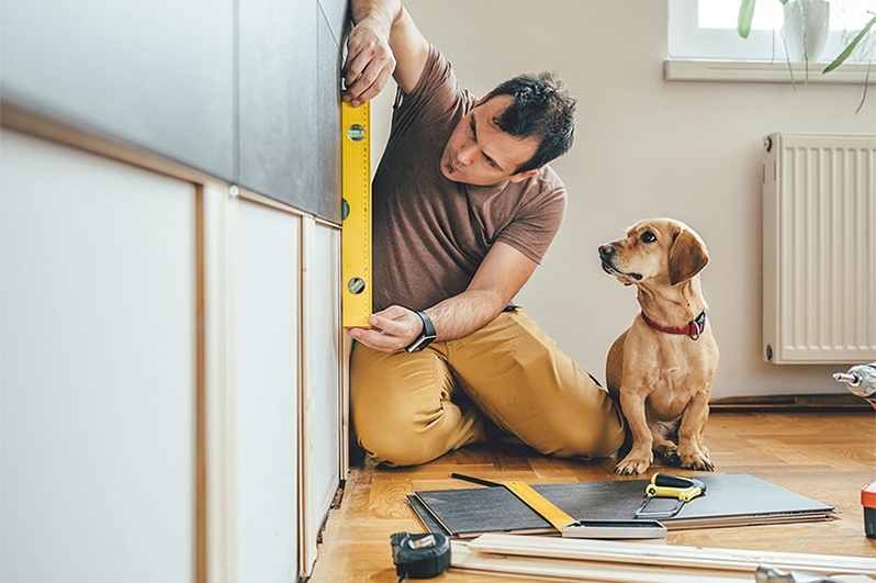 Man working on home with his dog