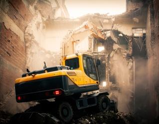 machine demolishing building